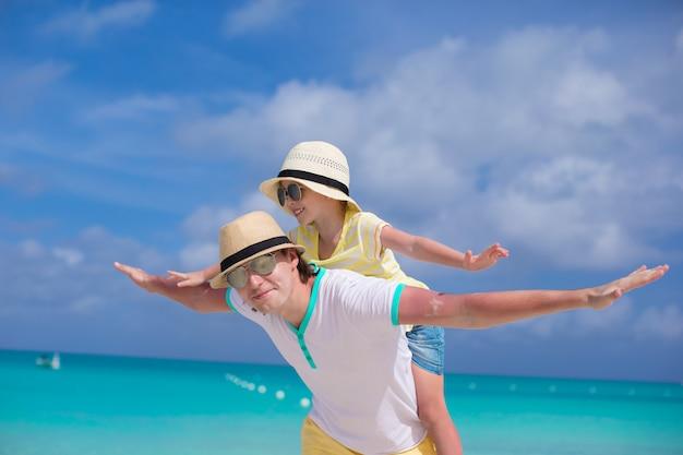 Feliz pai e sua adorável filha se divertir na praia tropical