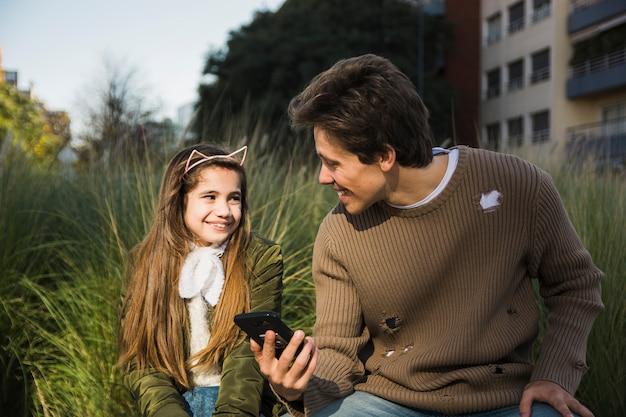Feliz, pai filha, olhando um ao outro, segurando, telefone móvel, em, mão