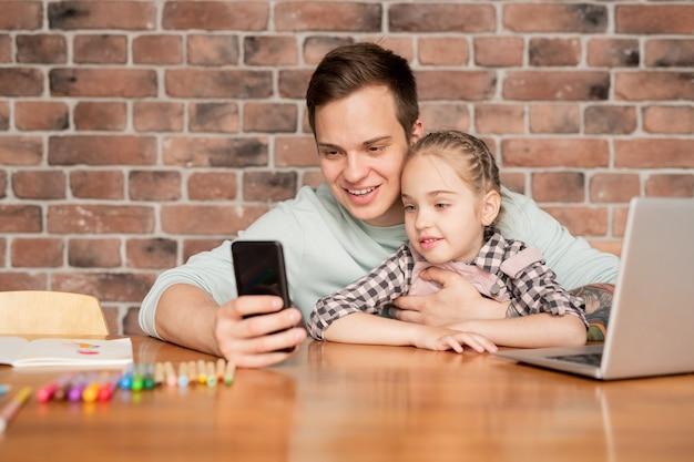 Feliz pai jovem bonito com tatuagem sentado à mesa em um apartamento e tirando selfie com a filha para enviar foto para a mãe