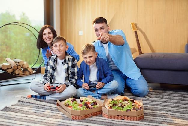 Feliz pai, mãe e dois filhos sentados no chão, jogando videogame com gamepads e comendo uma pizza saborosa