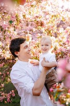 Feliz pai segura o filho nos braços, brincando com ele no contexto de um jacarandá no jardim