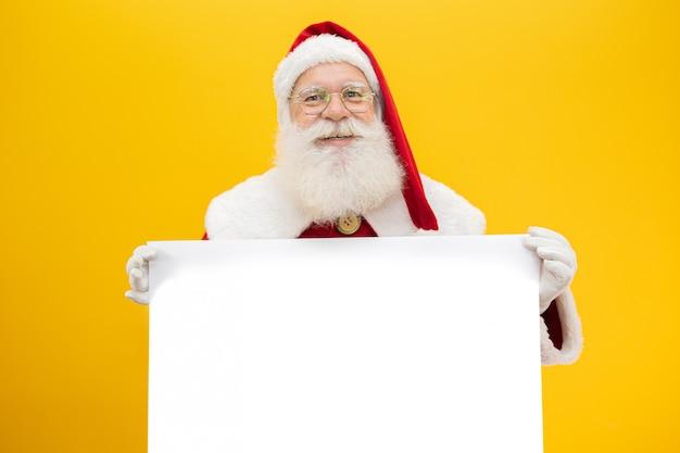 Feliz papai noel, olhando por trás do sinal em branco isolado em fundo amarelo, com espaço de cópia