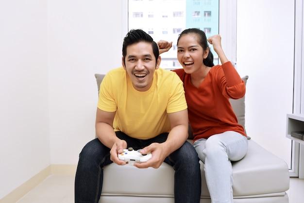 Feliz, par asiático, sentar sofá, e, videogame jogando