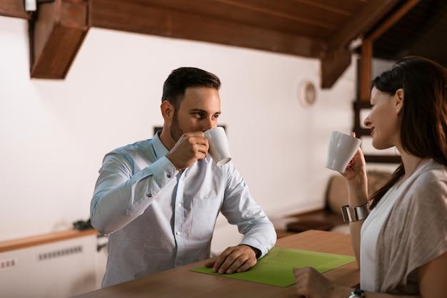 Feliz, par jovem, café bebendo, em, sala de estar
