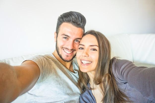 Feliz, par jovem, levando, um, selfie, com, câmera móvel esperto telefone, em, a, sala de estar, abraçar