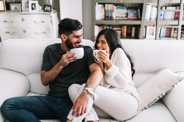 Feliz, par jovem, sentar sofá, xícara branca café