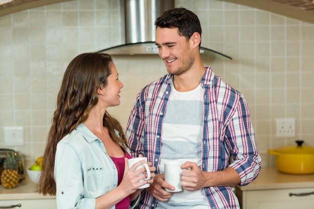 Feliz, par jovem, tendo, um, xícara café, em, cozinha