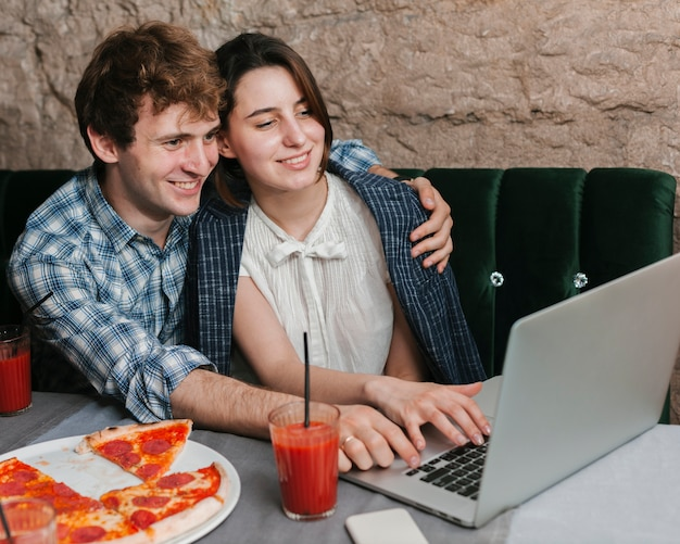 Feliz, par jovem, usando computador portátil