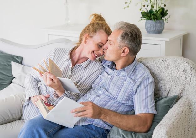 Feliz, par velho, com, livros, ligado, um, sofá