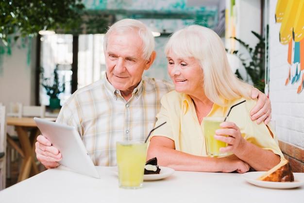 Feliz, par velho, em, café, desfrutando, refrescar, bebida, e, usando, tablete