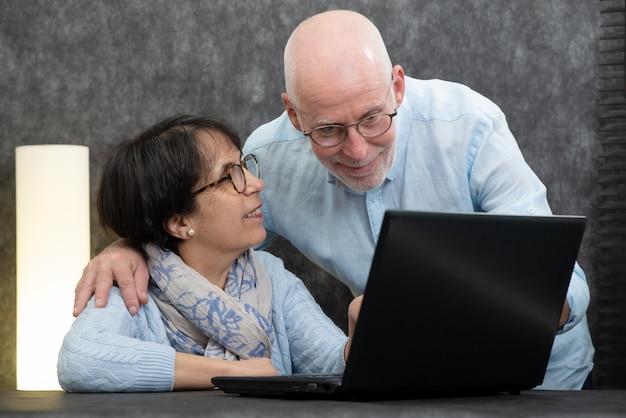 Feliz, par velho, usando computador portátil, casa
