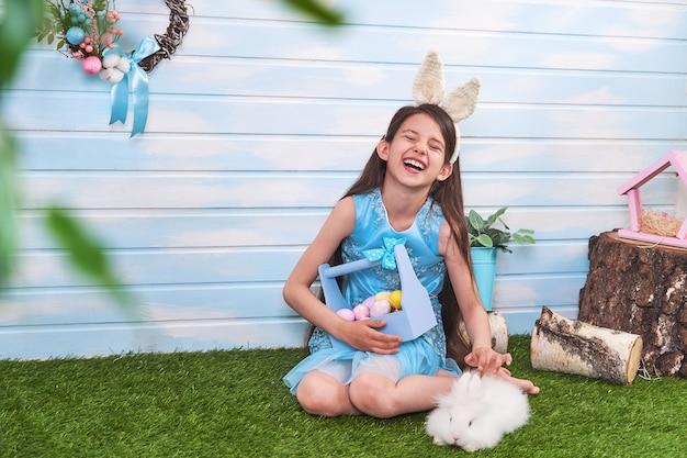 Feliz páscoa! bebê fofo usando orelhas de coelho no dia da páscoa. acariciando coelho branco.