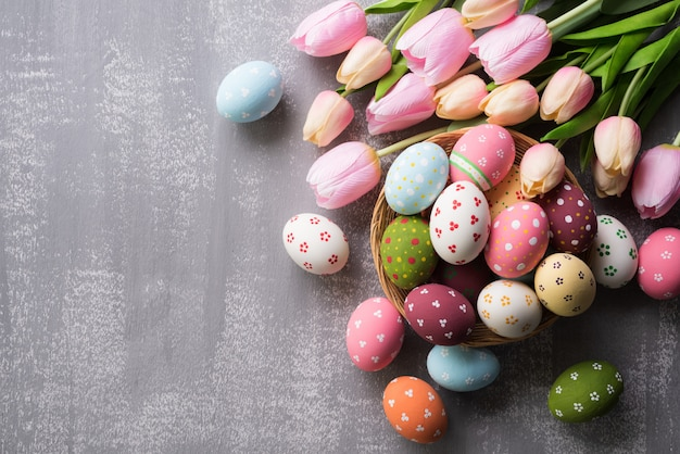 Feliz páscoa! colorido de ovos de páscoa no ninho com flor tulipa rosa