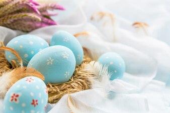 Feliz Páscoa! Colorido dos ovos da páscoa com a flor no fundo branco do cheesecloth.