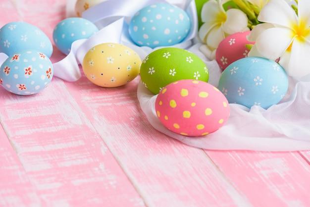 Feliz páscoa! colorido dos ovos da páscoa no ninho com a flor na parte traseira de madeira branca de gaze