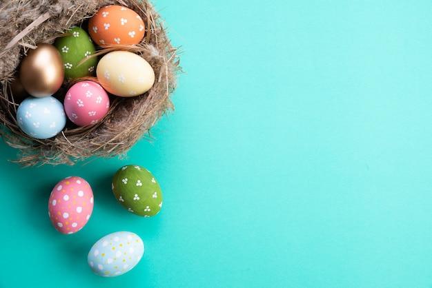Feliz páscoa! colorido dos ovos da páscoa no ninho no fundo de papel pastel verde.
