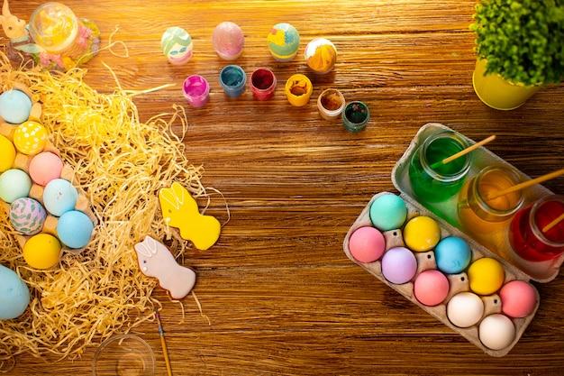 Feliz páscoa com ovos coloridos na cesta. decoração de mesa para férias. vista do topo.