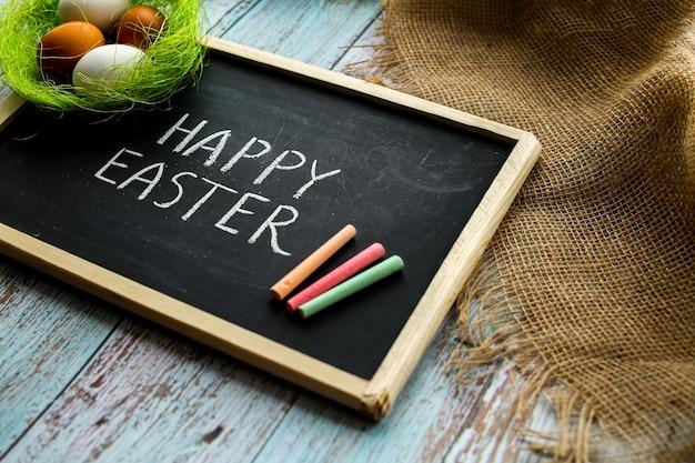 Feliz páscoa composição. ovos no ninho, quadro-negro com um desejo. rústico tradicional. fundo de madeira. foto de alta qualidade