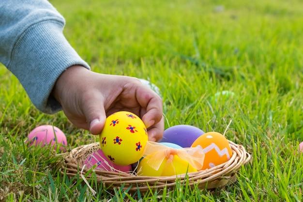 Feliz páscoa. conceito de ovos de páscoa. um menino que recolhe o ovo colorido no parque.