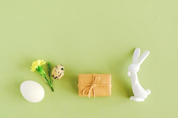 Feliz páscoa conceito. vários ovos, flores, artesanato presente e estatueta de coelho sobre fundo verde, com espaço de cópia
