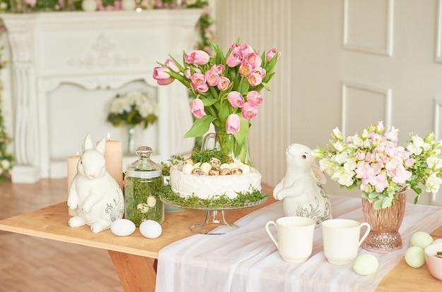 Feliz páscoa! decorações de férias. belo cenário festivo de mesa de páscoa com coelho, flores e ovos. tema de cor de primavera, cópia espaço. modelo de cartão de páscoa interier de cozinha.
