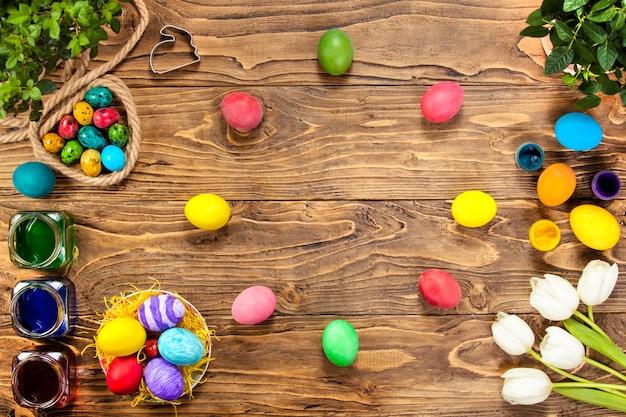 Feliz páscoa! desenha ovos de páscoa. ovos de páscoa e tulipas em tábuas de madeira. muito espaço livre para texto. tirada da vista superior. ovos de codorna lindamente pintados. frascos com corante
