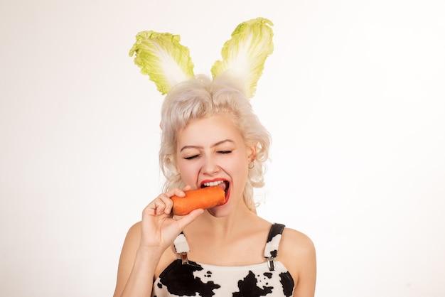 Feliz páscoa e engraçado dia de páscoa. jovem mulher usando orelhas de coelho no dia da páscoa. coelhinha surpresa come cenoura.