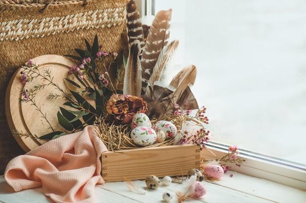 Feliz páscoa fundo. ovos de páscoa rosa em um ninho com decorações florais e penas perto da janela