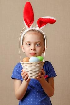 Feliz páscoa. garota de criança com orelhas de coelho e ovos.