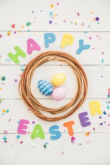 Feliz páscoa inscrição com ovos coloridos na mesa