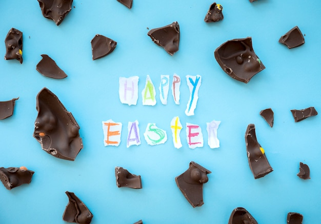 Feliz páscoa inscrição com pedaços de chocolate