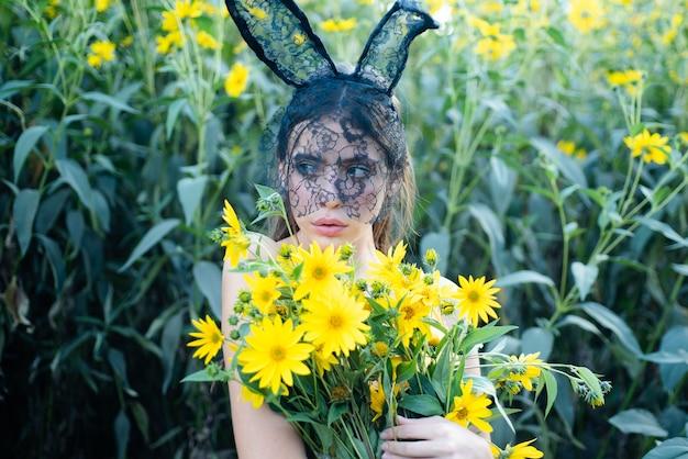Feliz páscoa. mulher coelhinha da primavera com flores. garota coelho lá fora. buquê de flores.
