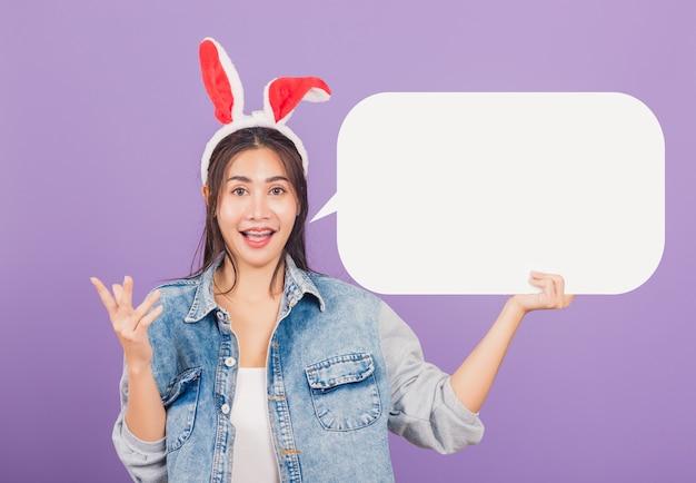 Feliz páscoa. mulher sorrindo animada usando orelhas de coelho segurando um balão vazio