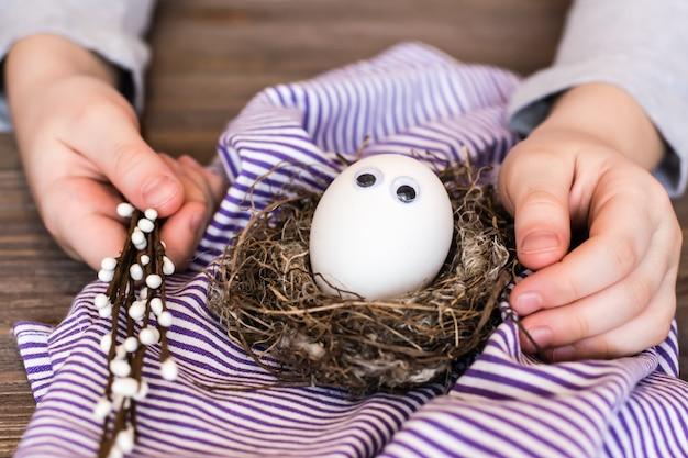 Feliz páscoa. ovo sem pintura com olhos no ninho de um pássaro, mãos de crianças e ramos de salgueiro em uma mesa de madeira.
