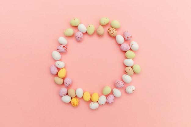 Feliz páscoa. ovos de chocolate doces de páscoa e doces de jujuba, isolados no fundo rosa pastel na moda. minimalismo simples plana leigos vista superior cópia espaço