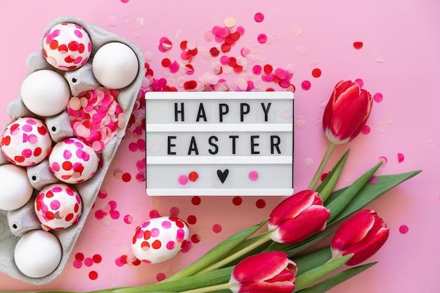 Feliz páscoa. ovos de páscoa decorados com confetes de papel e tulipas