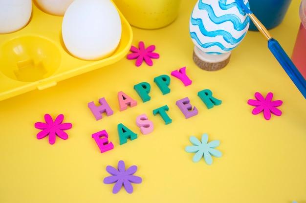 Feliz páscoa palavra feita de letras coloridas com flores de madeira, ovos na bandeja de ovos amarelos, tintas e pincéis pintando ovos em ondas azuis sobre fundo amarelo.