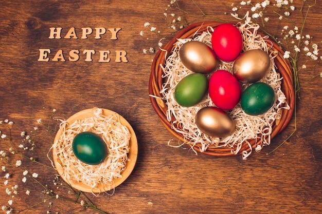 Feliz páscoa palavras perto de ovos brilhantes em pratos com ouropel perto de plantas