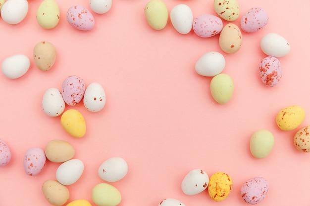 Feliz páscoa. preparação para férias. ovos de chocolate doces de páscoa e doces de jujuba, isolados no fundo rosa pastel na moda. simples minimalismo plana leigos vista superior cópia espaço.