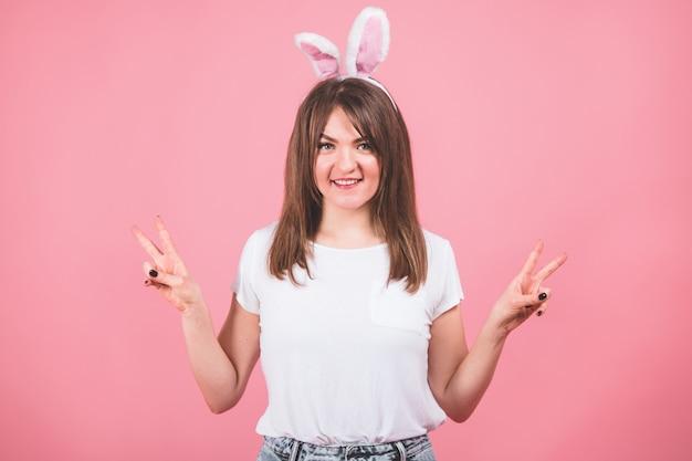 Feliz páscoa. retrato de uma linda garota com orelhas de coelho em pé isolado sobre o rosa