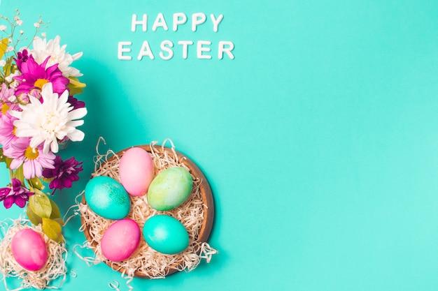 Feliz páscoa título perto de ovos brilhantes no buquê de flores e placa