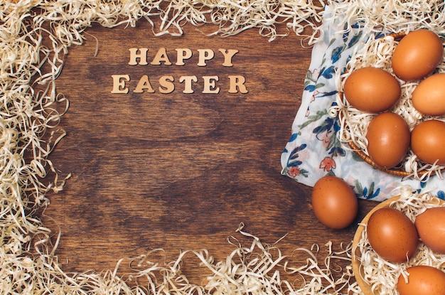 Feliz páscoa título perto de ovos de galinha em tigelas em material florido entre ouropel a bordo