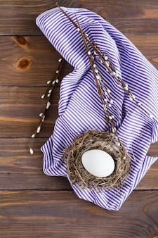 Feliz páscoa. um ovo de galinha branca no ninho de um pássaro e ramos de salgueiro em uma mesa de madeira. estilo rústico. copie o espaço.