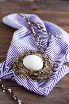 Feliz páscoa. um ovo de galinha branca no ninho de um pássaro e ramos de salgueiro em uma mesa de madeira. estilo rústico