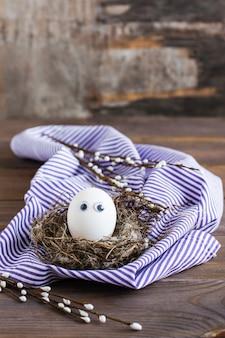 Feliz páscoa. um ovo de galinha sem pintura com olhos no ninho de um pássaro e ramos de salgueiro em uma mesa de madeira. .