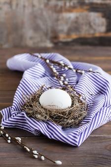 Feliz páscoa. um ovo de galinha sem pintura no ninho de um pássaro e ramos de salgueiro em uma mesa de madeira. .