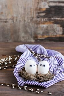 Feliz páscoa. um par de ovos sem cor com olhos no ninho de um pássaro e ramos de salgueiro em uma mesa de madeira.