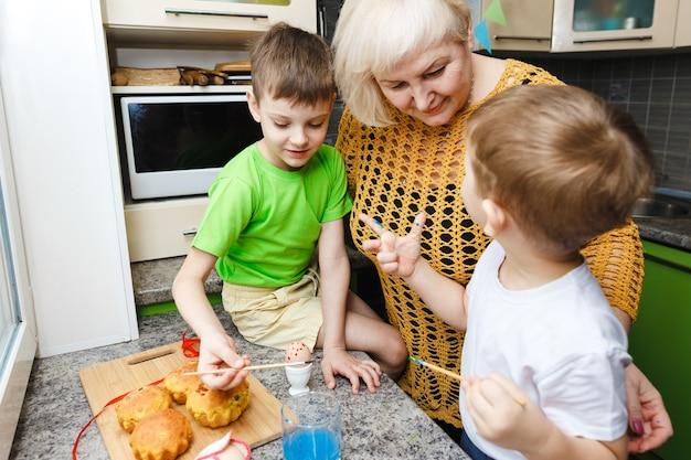 Feliz páscoa. uma avó e seus netos pintando ovos de páscoa. família feliz se preparando para a páscoa em casa