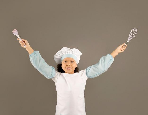 Feliz pequeno chef segurando utensílios de cozinha