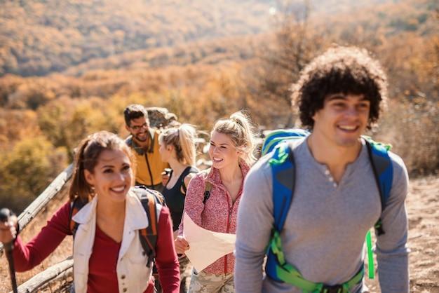 Feliz pequeno grupo de caminhantes andando na fila no outono. foco seletivo na mulher loira.